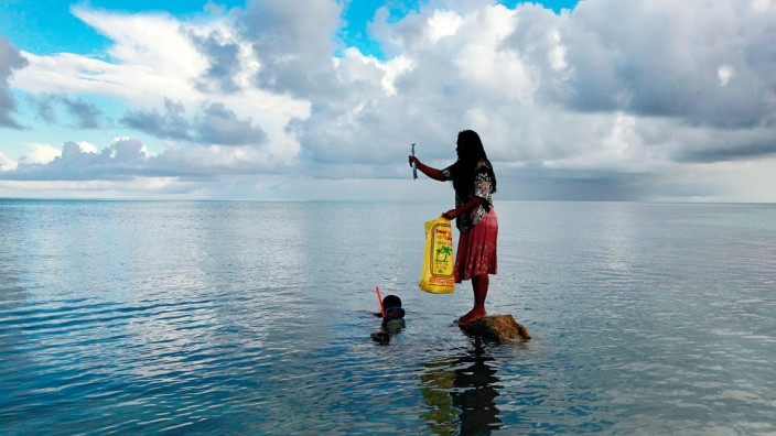 Binata Pinata stands on top of a rock holding a fish her husband Kaibakia just caught on Bikeman Islet, located off South Tarawa in the central Pacific island nation of Kiribati