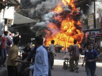 Residents run from a fire at a gasoline and oil shop in Bustan Al-Qasr