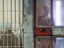 An inmate looks out from his cell in the Secure Housing Unit at Corcoran State Prison in California