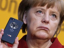File photo of German Chancellor Merkel holding a smartphone featuring high security Secusite software in Hanover