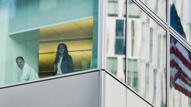 Office workers inside of the Goldman Sachs headquarters smile as they watch Occupy Wall Street demonstrations below their building on the one-year anniversary of the movement in New York