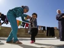 Ein Mädchen in Syrien hilft ihrem kleinem Bruder, der vermutlich an Polio erkrankt ist