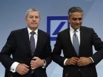 Fitschen and Jain, co-chairmen of the Germany's largest business bank, Deutsche Bank AG close their jackets after the annual news conference in Frankfurt