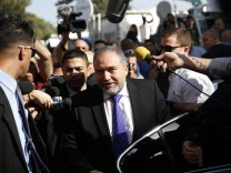 Former Israeli Foreign Minister Lieberman, steps out of a car as he arrives to hear the verdict in the corruption charges against him at the Magistrate Court in Jerusalem