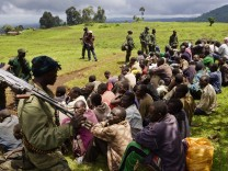 Congolese soldiers guard suspected M23 rebel fighters who surrendered in Chanzo village in the Rutshuru territory near the eastern town of Goma