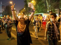 A supporter of moderate cleric Hassan Rohani gestures with a picture of him as she celebrates his victory in Iran's presidential election on a street in Tehran