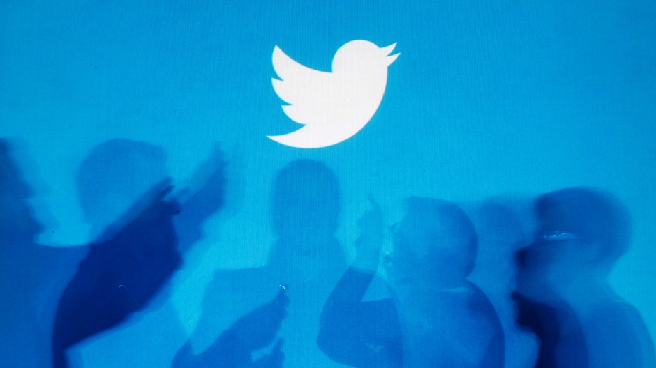 File illustration photo shows shadows of people holding mobile phones cast onto a backdrop projected with the Twitter logo