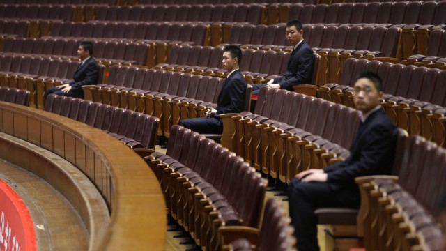 Security personnel sit inside the Great Hall of the People in Beijing