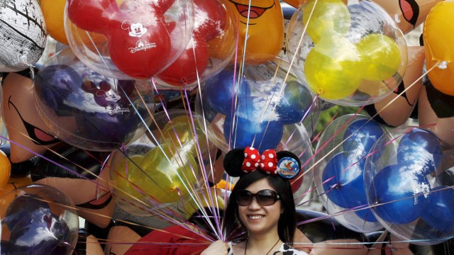 A visitor holds balloons as she has her photo taken by her friend at the Hong Kong Disneyland