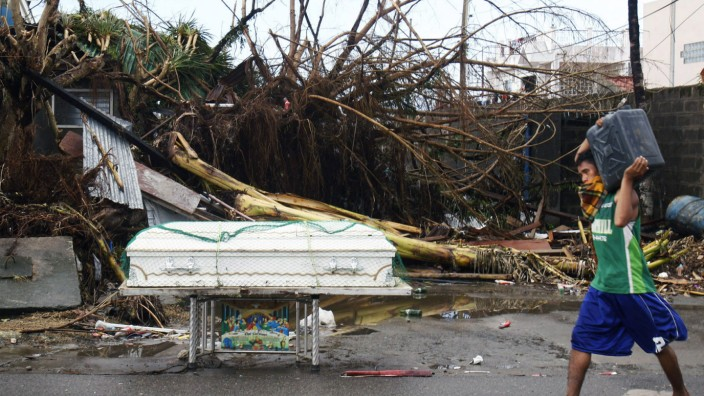 A passer-by walks next to a coffin along a street after super typhoon Haiyan battered Tacloban City, in central Philippines