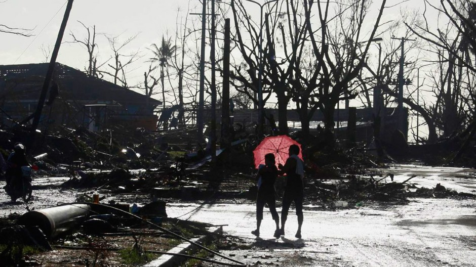 Couple carrying their sick child walk to a Philippine Red Cross service centre in Tacloban