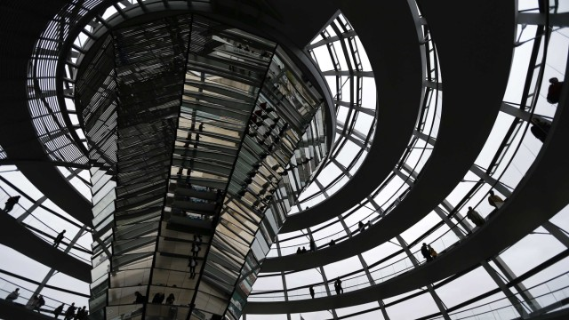 People walk inside the dome of the Reichstag building in Berlin