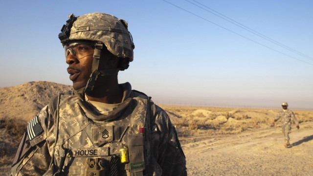Staff Sergeant House assembles his team back to their MRAP vehicle after crossing the Kuwaiti border as part of the last U.S. military convoy to leave Iraq