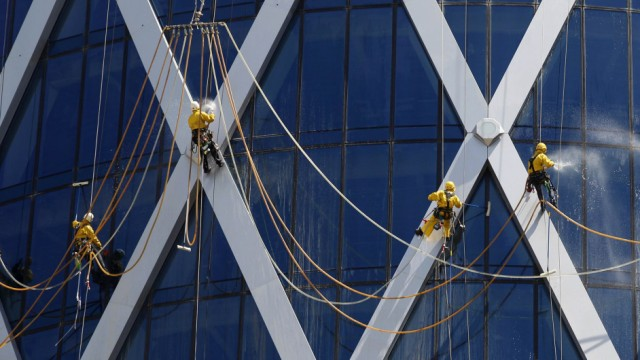 Workers suspended on ropes clean the glass windows of the Tornado tower in Doha