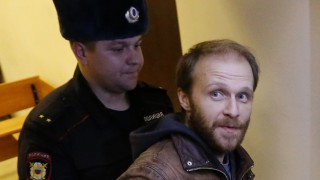 Photographer Denis Sinyakov is escorted during a break in a court session before the announcement of the verdict in St. Petersburg