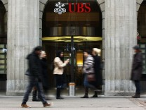 File photo of people walking in front of a branch of Swiss bank UBS in Zurich