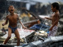 Children shower near the debris of an area destroyed by Typhoon Haiyan in Tacloban City