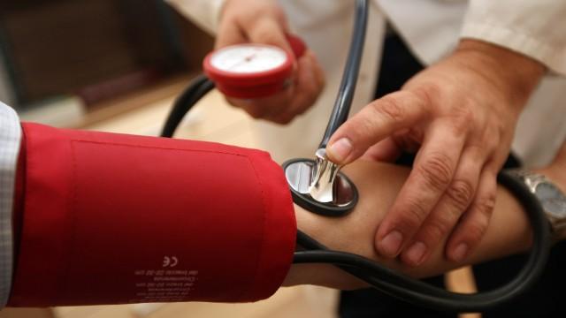 Hausarzt auf Hausbesuch: Ein Arzt misst den Blutdruck seiner Patientin in deren Wohnung.