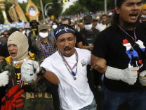 Anti-government protesters shout as they get ready to attack a police barricade near the Government house in Bangkok