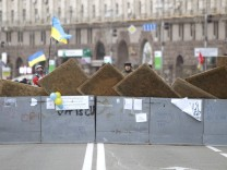 Protesters are seen near barricades which blocked the main avenue in Kiev