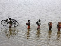 People from a nearby village carry their belongings through floodwaters at Ganjam district in Odisha