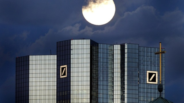 A rising full moon is seen over the twin towers of Germany's Deutsche Bank headquarters in Frankfurt