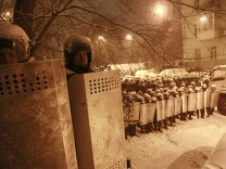 Interior Ministry personnel block a street during a gathering of supporters of EU integration during snowfall in Kiev