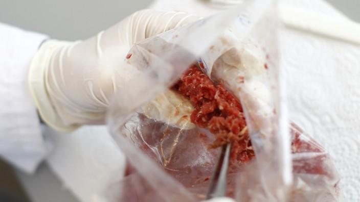 Employee Hess takes a sample of minced meat in food control laboratory institute Eurofins in Ebersberg