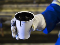 A worker holds a cup of heavy oil before it is shipped to the market at the Cenovus Energy Christina Lake SAGD project south of Fort McMurray