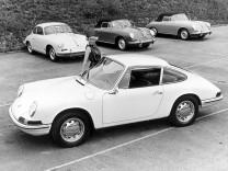 Eine Werbung für einen Porsche 911, dahinter sind drei Porsche 356 platziert.