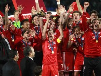 Lahm of Germany's Bayern Munich holds the trophy as he celebrates with his team-mates winning their 2013 FIFA Club World Cup final soccer match against Morocco's Raja Casablanca at Marrakech stadium