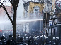 German police use water cannons to clear a street following clashes in front of the 'Rote Flora' cultural centre during a demonstration in Hamburg