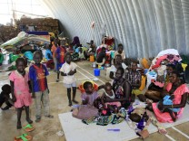 Families displaced by recent fighting in South Sudan, camp in a warehouse inside the UNAMIS facility in Jabel