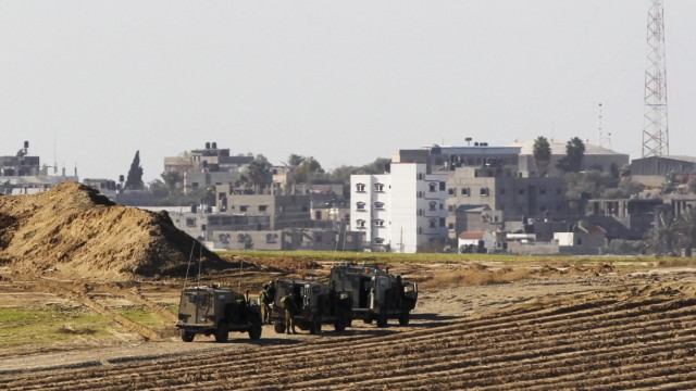Israeli military jeeps are seen at the scene of a shooting incident near the border with the northern Gaza Strip