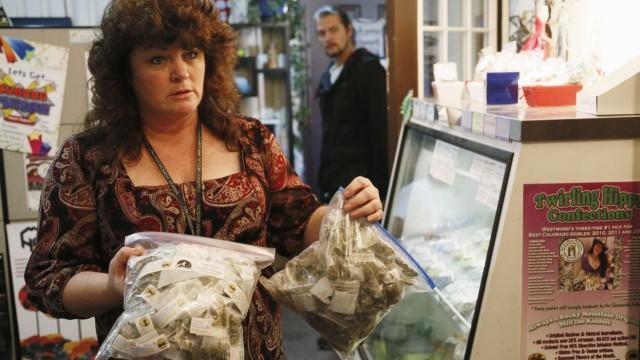 Cheri Hackett, co-owner of BotanaCare, carries bags of the company's sample packs of marijuana in Northglenn, Colorado