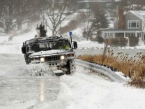A police vehicle drives through a flooded street during a winter nor'easter snow storm in Scituate