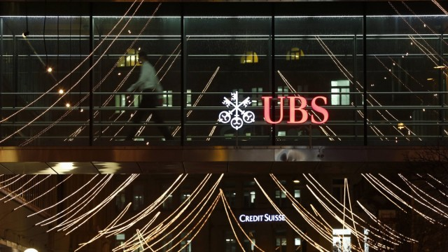 A man walks past the logo of Swiss Bank UBS on a footbridge connecting two office buildings in Zurich
