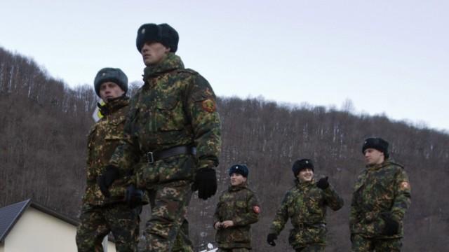 Russian servicemen walk along a road near the resort of Krasnaya Polyana