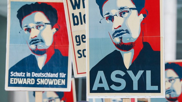 Demonstrators hold banner during protest rally in support of Snowden in Berlin