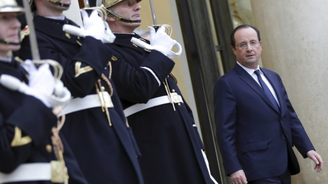 French President Hollande stands on the stairs of the entrance of the Elysee Palace in Paris after a meeting
