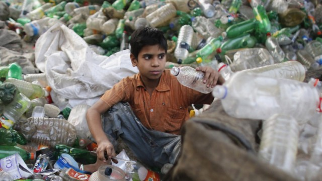 A boy works at a plastic bottle recycling centre by the river Buriganga in Dhaka