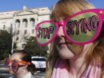 Member of protest group, Code Pink, Cayman Macdonald  protests against U.S. President Obama and NSA before his arrival at Department of Justice in Washington