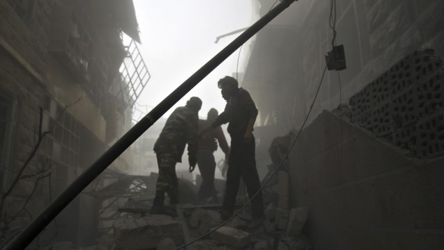Residents look for survivors amid damaged buildings after what activists said was an air strike by forces loyal to Syria's president Al-Assad in the Al-Ansari neighborhood of Aleppo
