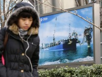 A woman walks past a poster showing an offshore work platform from CNOOC in Beijing