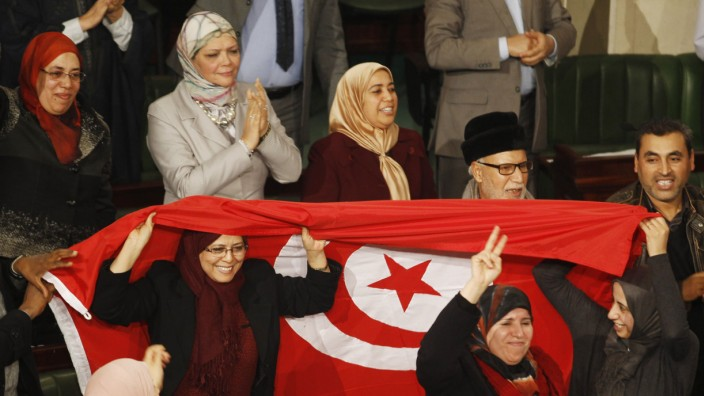 Members of the Tunisian parliament wave flags after approving the country's new constitution in the assembly building in Tunis