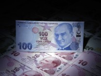 A Turkish 100 lira banknote is seen on top of 10 lira banknotes in this illustration picture taken in Istanbul