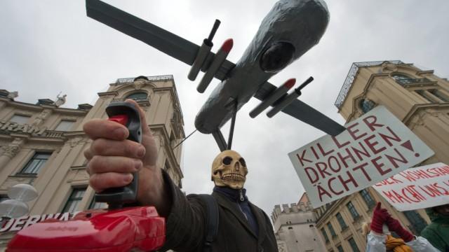 Ein als Tod verkleideter Mann mit einer Drohne über dem Kopf und einem roten Steuerhebel in der Hand nimmt am 02.02.2013 an einer Demonstration gegen die 49. Münchner Sicherheitskonferenz in der Innen