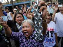 Protesters demanding the right to vote break into the district office after voting was called off in Din Daeng district in Bangkok