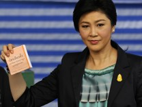 Thai Prime Minister Yingluck Shinawatra shows her ballot before casting it at a polling station in Bangkok