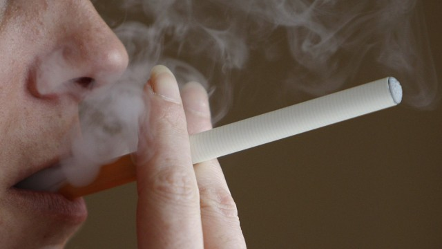 Woman smokes an E-cigarette, an electronic substitute in the form of a rod, in Bordeaux